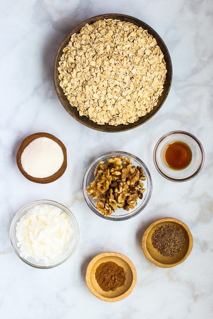 Bowls of oats, erythritol, walnuts, flax, vanilla, coconut flakes and cinnamon on white marble.