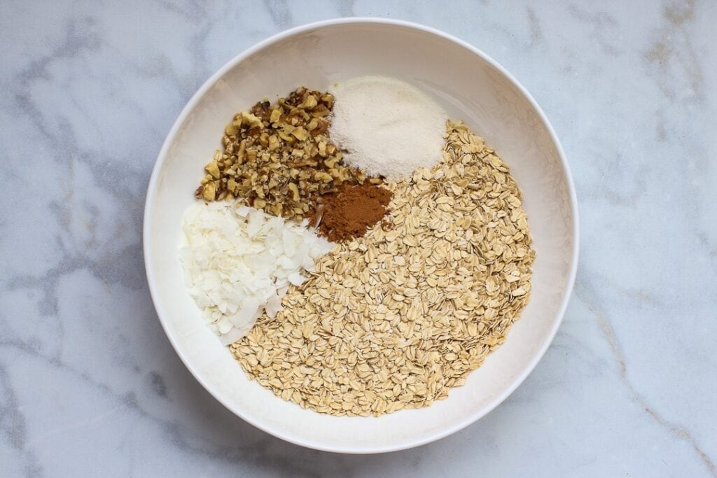 White bowl with oats, chopped nuts, coconut flakes, cinnamon and erythritol on white marble.