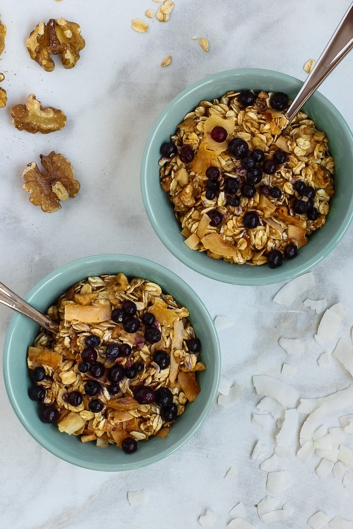 Two aqua bowls of granola with blueberries and spoons on white marble, with walnuts, oats and coconut flakes.
