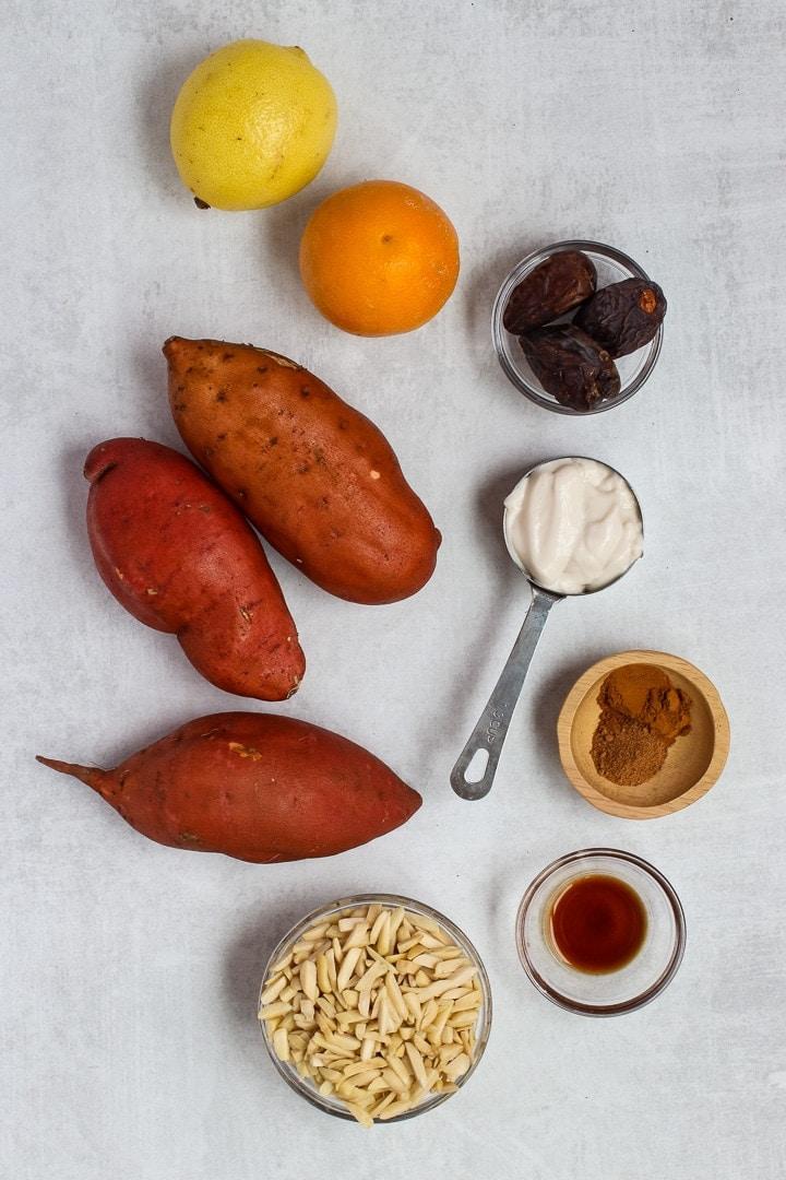 Sweet potatoes, lemon, orange, dates, slivered almonds, yogurt, spices and vanilla on a gray background.