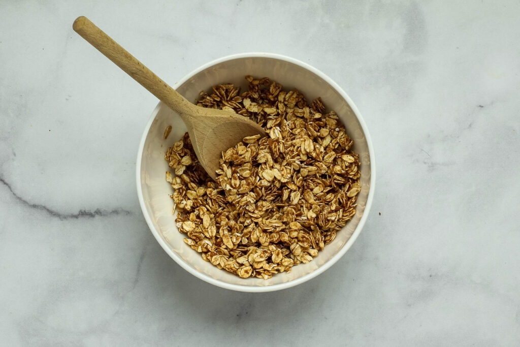 Tossing the oats, cinnamon and date paste in a mixing bowl.