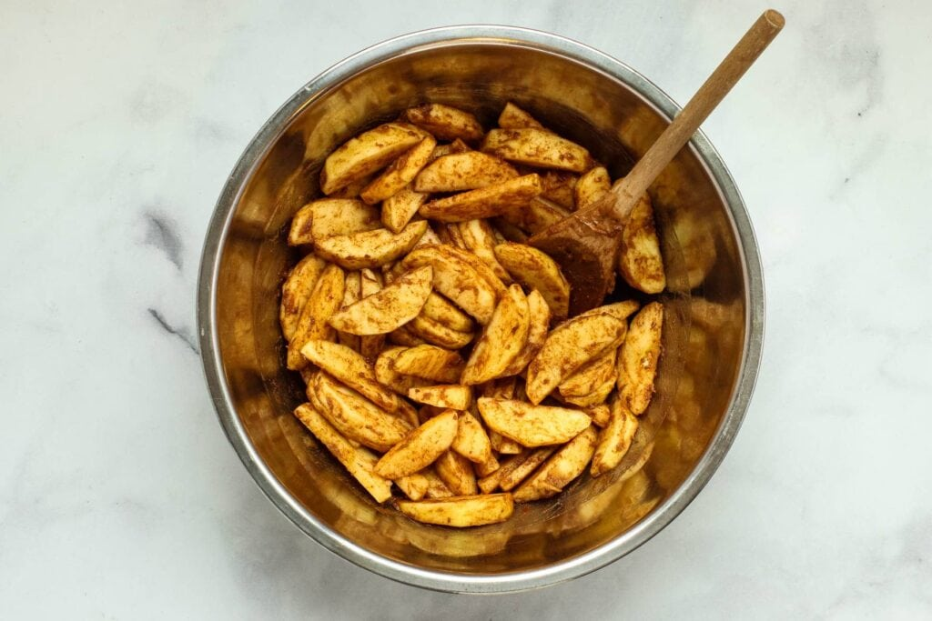 Tossing apple slices, cinnamon and date paste in a mixing bowl with a wooden spoon.