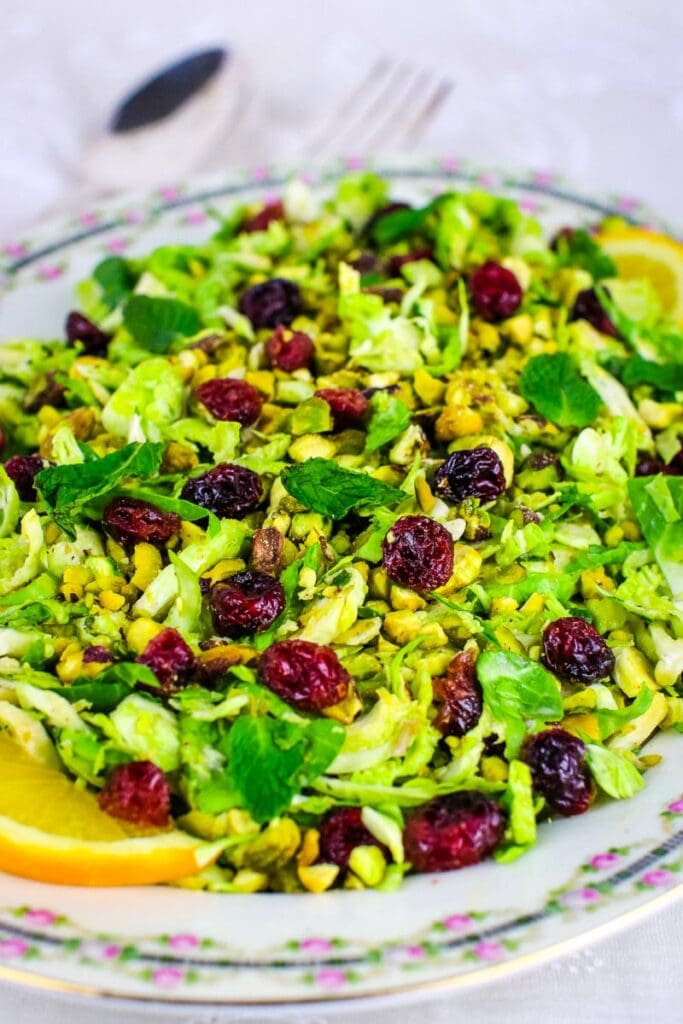 antique china platter with brussels sprouts salad with cranberries, spoon and fork in background