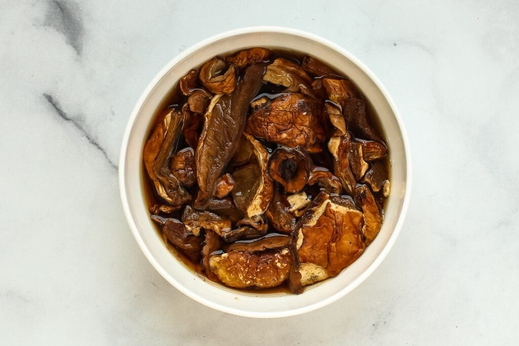 White ramekin of re-hydrating dried porcini mushrooms on white marble.