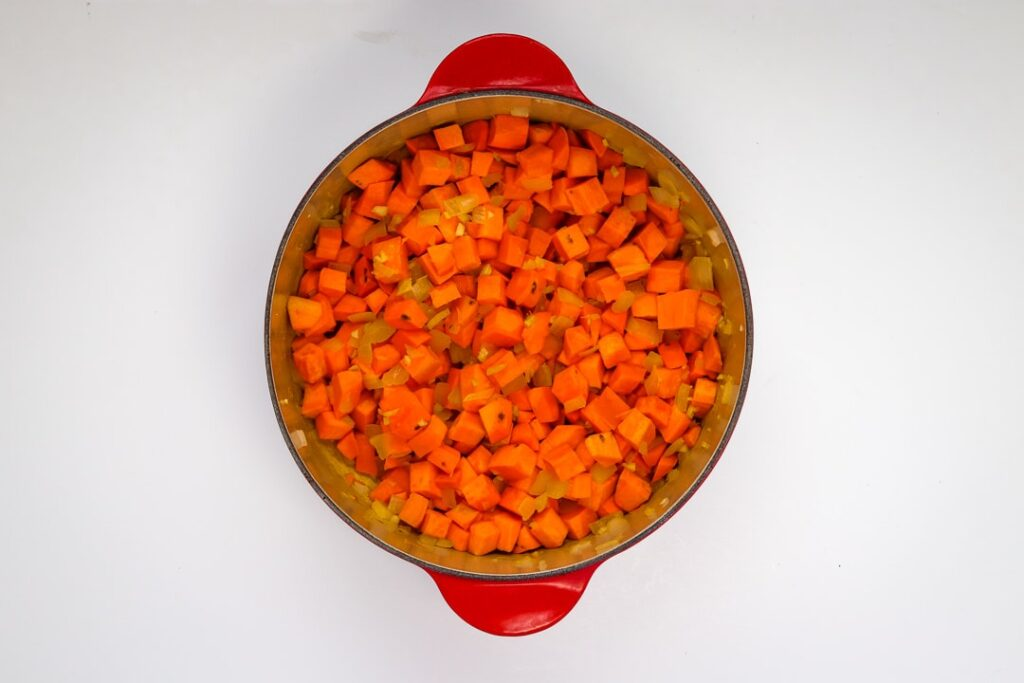 Sweet potatoes and aromatics simmering in a red dutch oven.