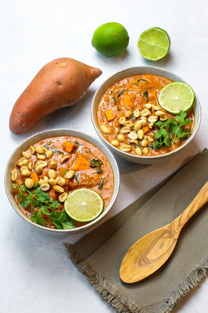 Two bowls of African peanut stew with lime slice, chopped peanuts and cilantro. Whole sweet potato , wooden spoon and cut lime in background.