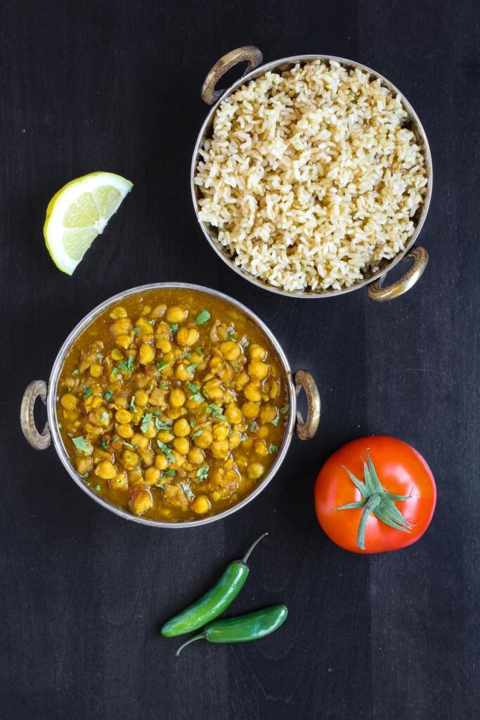 Overhead image of chana masala and rice in copper dishes on dark wood, with rice, tomato, jalapeno pepper and lemon slice.