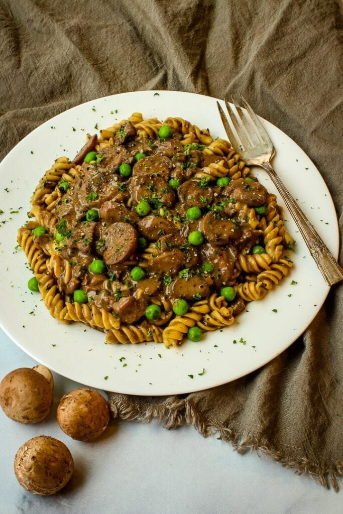 white plate with mushroom stroganoff over curly pasta, garnished with parsley, with fresh mushrooms and fork on the side.