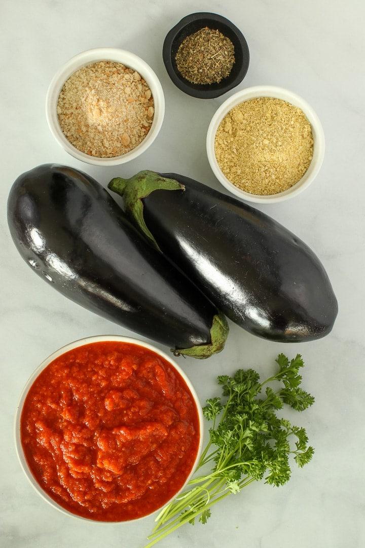 Vegan Eggplant Parmesan ingredients: Eggplants, tomato sauce, panic bread crumbs, vegan Parmesan, Italian Seasonings, optional fresh parsley.