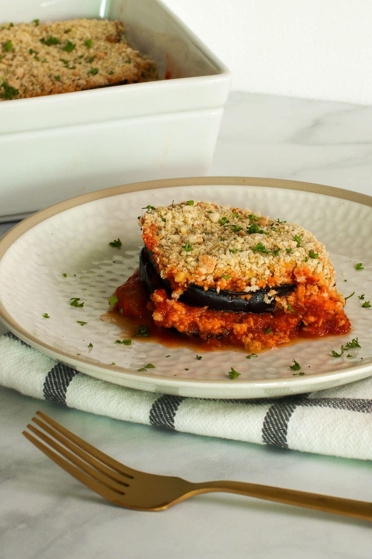 Vegan eggplant Parmesan slice on a white plate, with casserole dish in background. Gold fork, black plaid napkin.