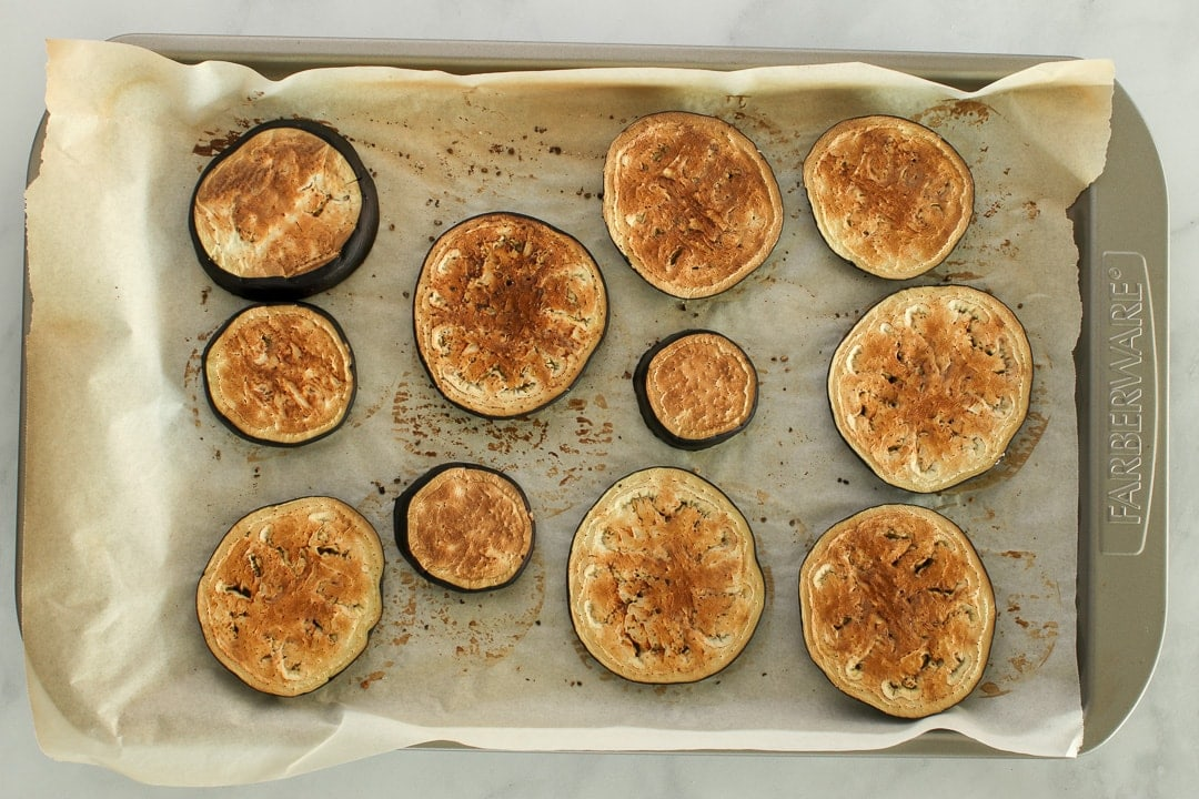 Roasted eggplant slices on a parchment paper lined baking sheet.