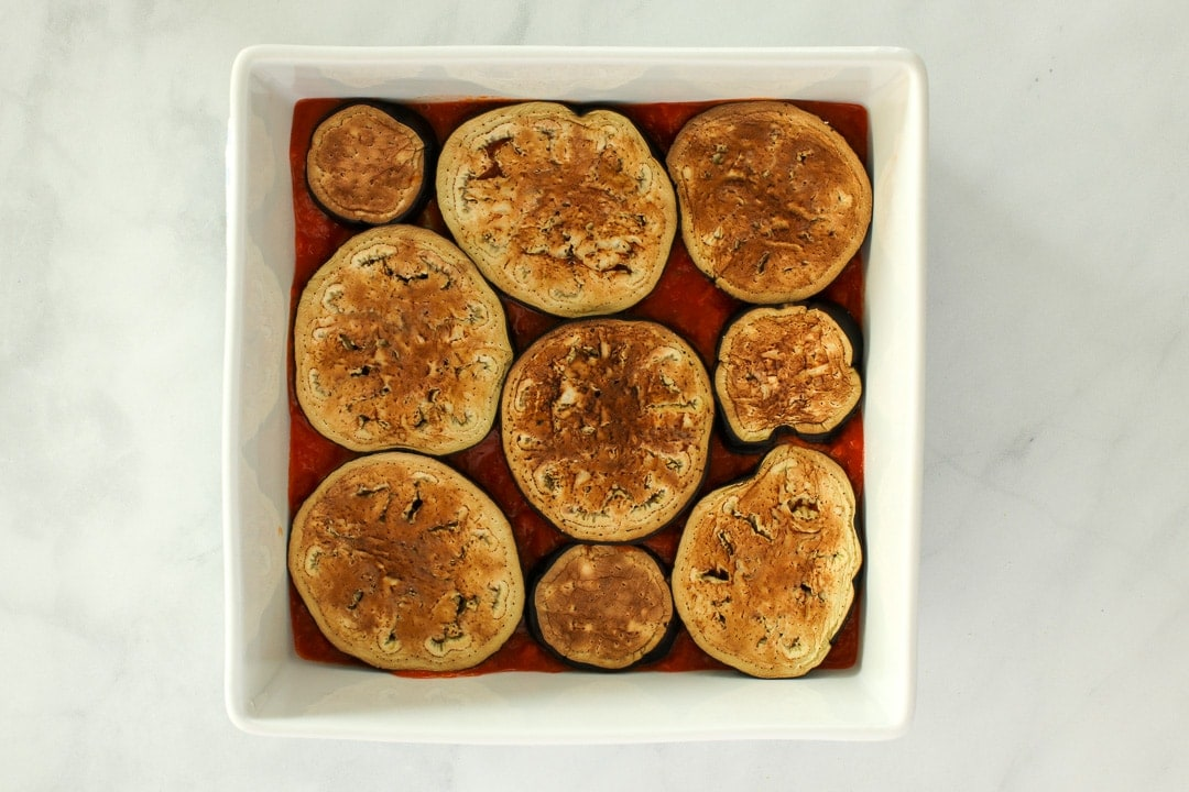 Layer roasted eggplant slices over the tomato sauce.