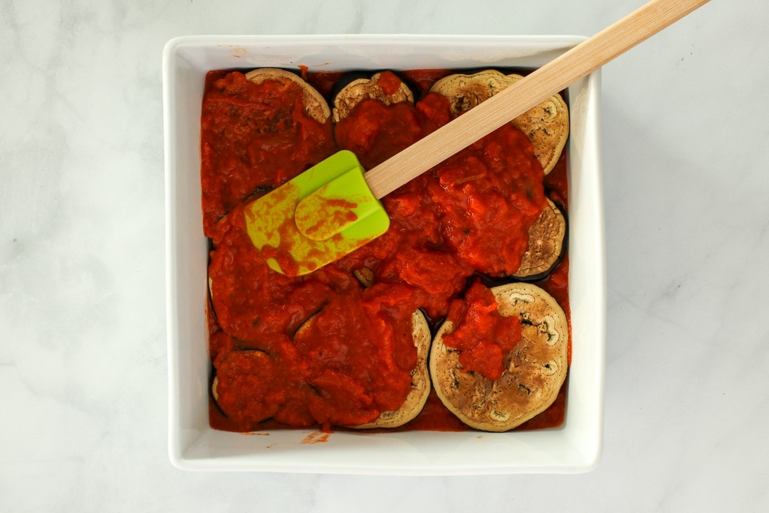 Top the eggplant slices with half the remaining tomato sauce.