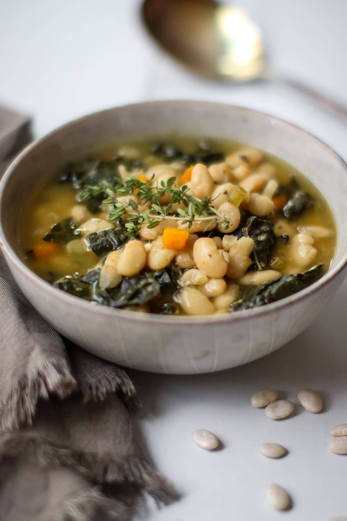 White bean soup with kale in a pale blue bowl with fresh thyme.