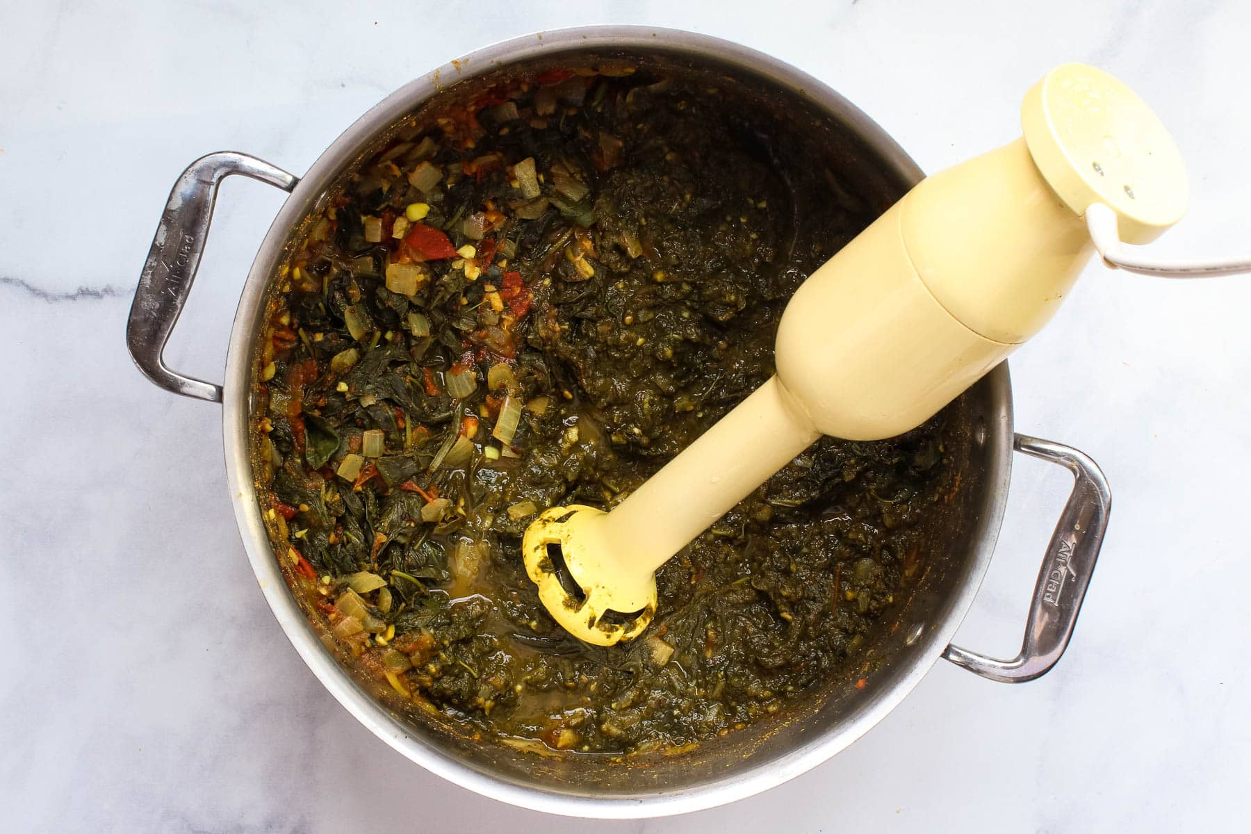 Blending spinach and other ingredients with an immersion blender.