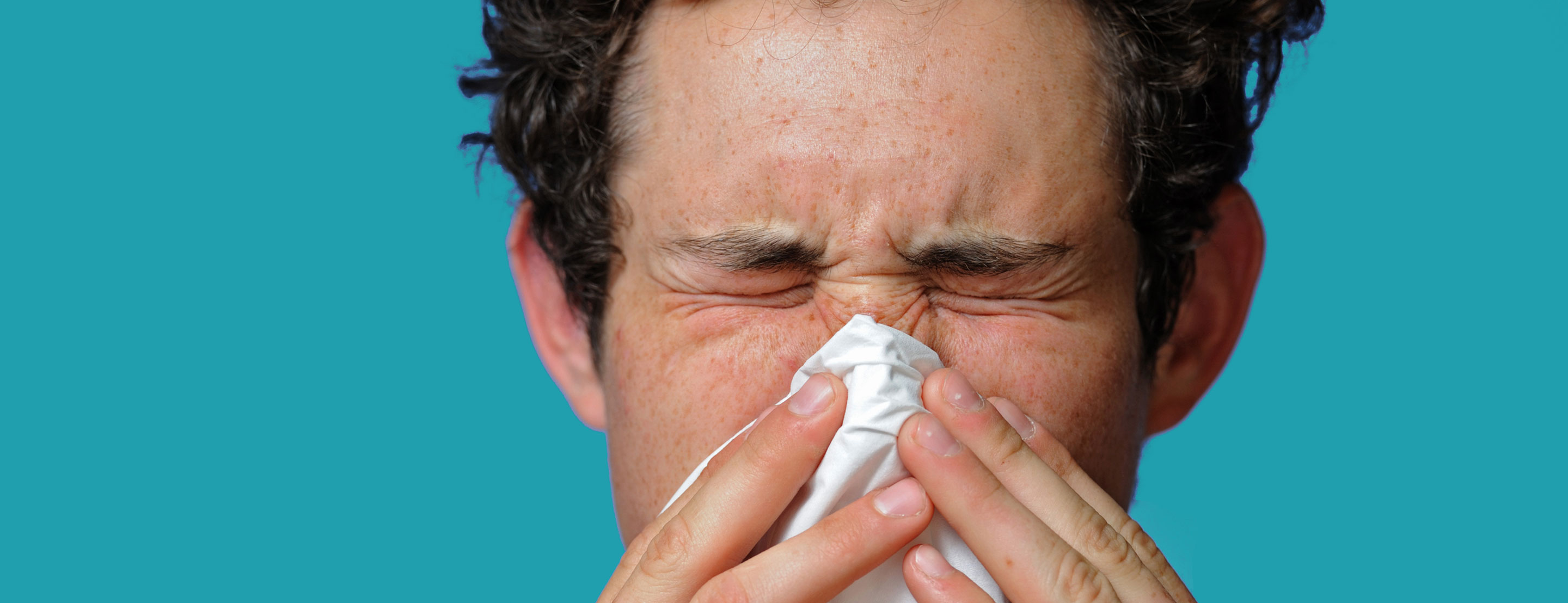 man sneezing from seasonal allergies