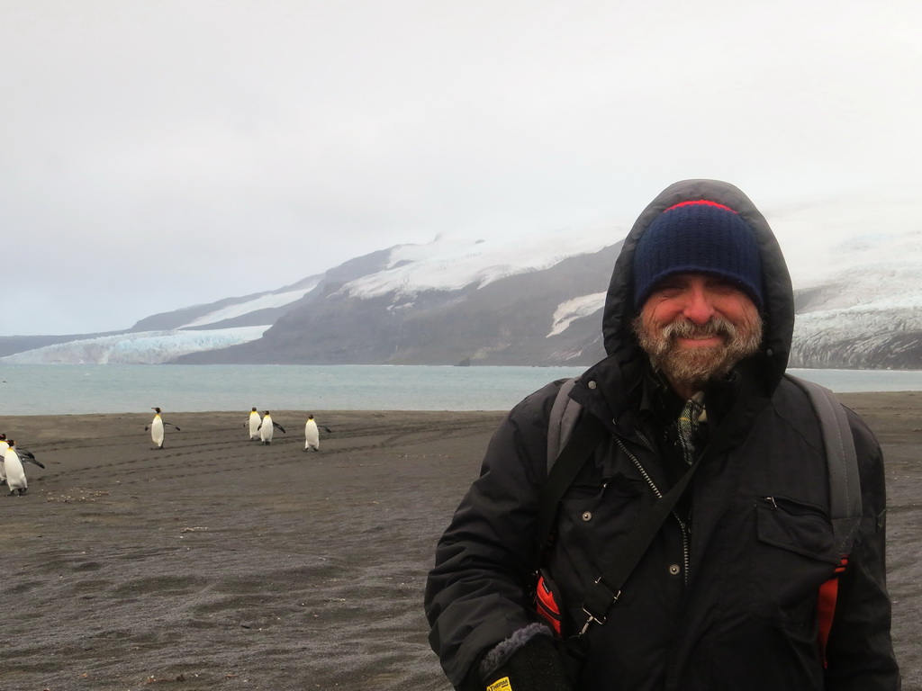 Expedition Organizer and Leader Robert Schmieder KK6EK on Heard Island. Behind him are a large bay and glaciers, lying in view from the VKØEK campsite.  Image credit: Bill Mitchell.