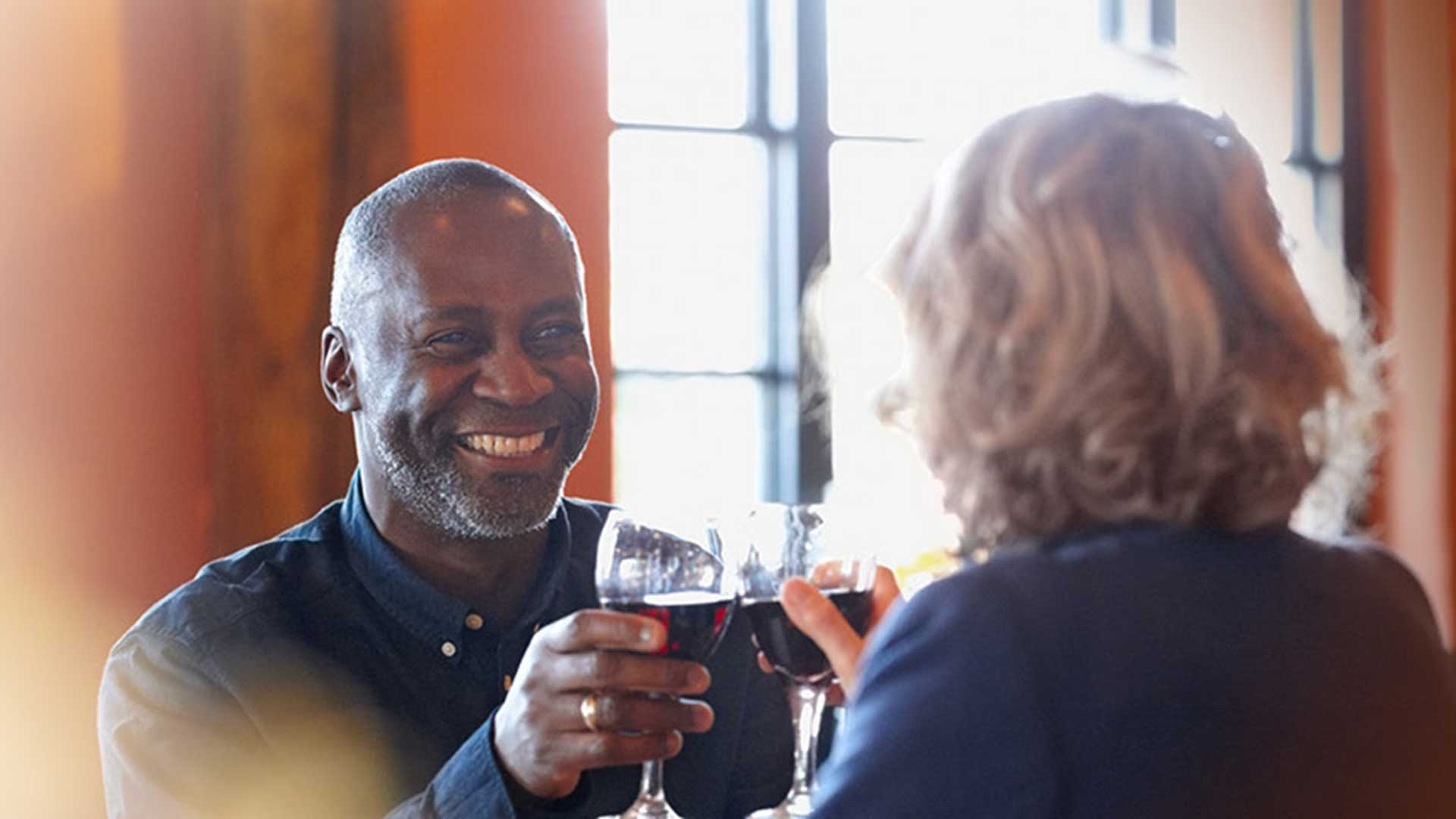an african american man smiles as he touches his wine glass to that of his wife as they dine free of hearing difficulties