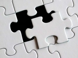 puzzle piece about to be put into a puzzle.