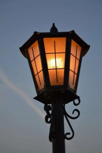Lamp post at dusk glowing with orange light.