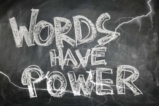 """A black chalkboard with """"words have power"""" written in thick chalk lines."""