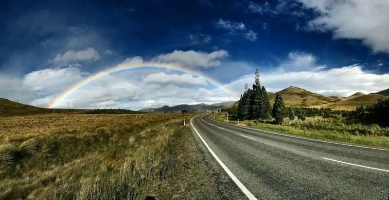 Highway leading to a rainbow in the distance.