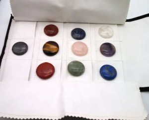Flat round chakra gemstones laid out on open foldable carrying case.