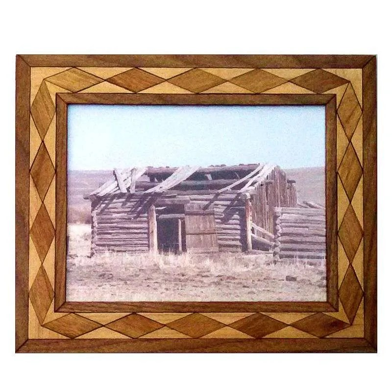 Photograph of old trapper cabin in handcrafted diamond pattern hardwood frame.