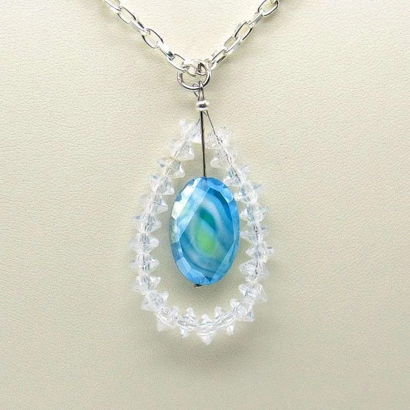 Blue glass teardrop pendant surrounded by crystals.