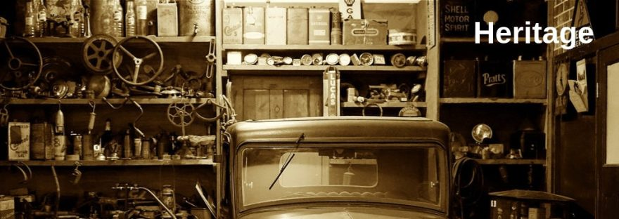 A sepia photo featuring an old car in a dusty shed.