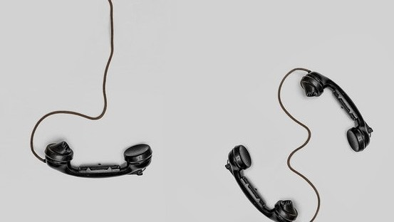 Two old black telephones with cord