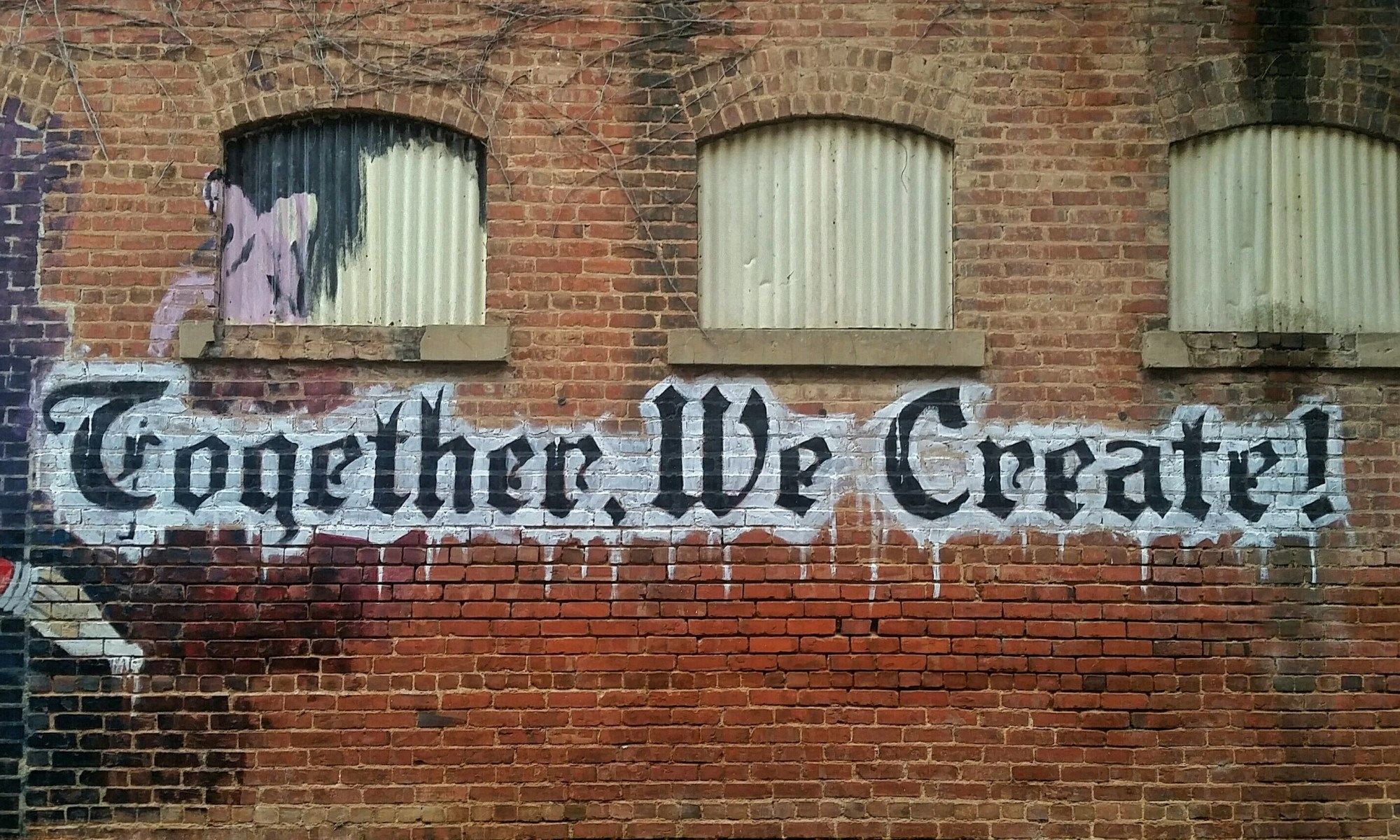 Graffiti: Together, We Create! on a brick wall
