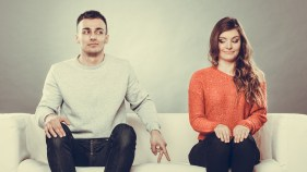 Shy woman and man. Guy sitting near attractive young woman on sofa and making hand gesture walking with finger to girl ** Note: Soft Focus at 100%, best at smaller sizes