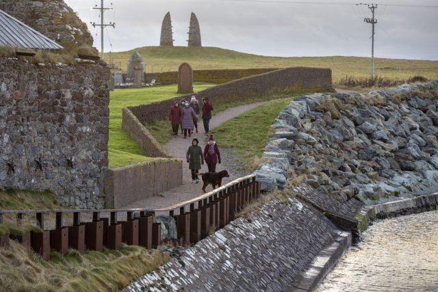 Walkers on the coastal path, along the perimeter of Eaglais na h-Aoidhe