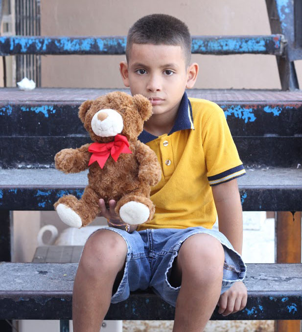 Nine-year-old+Angel+sits+on+the+steps+of+the+orphanage.+He+was+playing+with+his+toy+bear.+