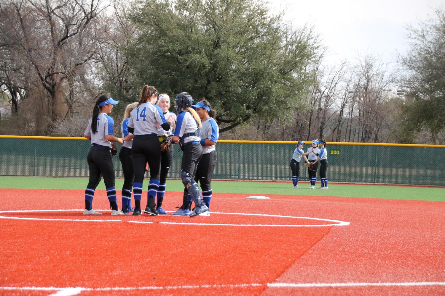 The softball team huddles around the pitcher's mound. They were discussing a strategy prior to the start of the inning.