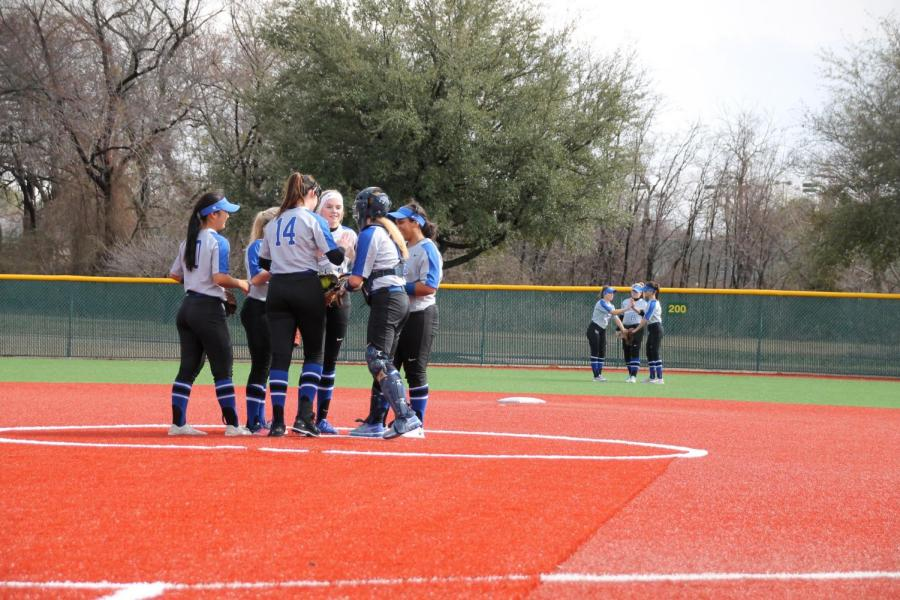 The+softball+team+huddles+around+the+pitcher%27s+mound.+They+were+discussing+a+strategy+prior+to+the+start+of+the+inning.