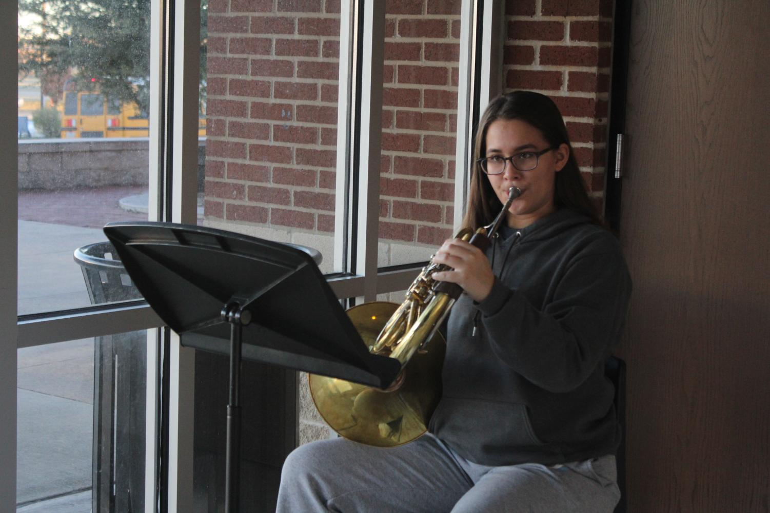 Junior Xinrae Cardozo warms up on her French horn before school. She is a three-time Area musician.