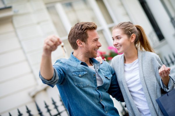 Excited couple buying a house and holding the keys