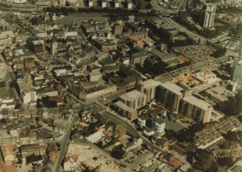 Bron: Rijckheyt.nl | Luchtfoto van het centrum van Heerlen met op de voorgrond het Algemeen Ziekenfonds voor de Mijnstreek (AZM) aan de Akerstraat. Op de achtergrond links het Glaspaleis en de St.Pancratiuskerk.