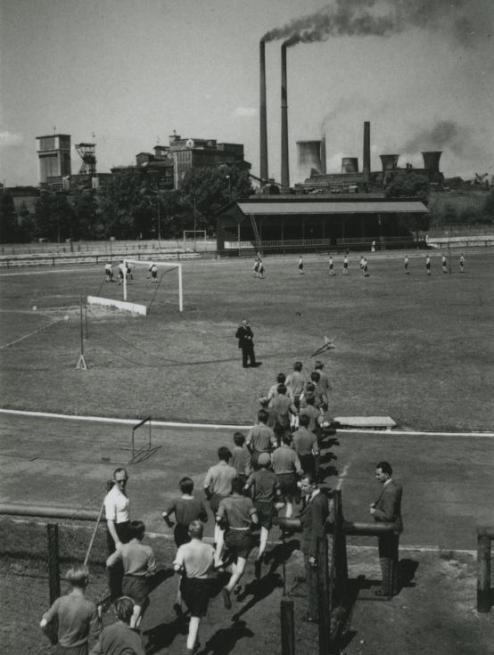 Bron: Rijckheyt.nl | Leerlingen van de Ondergrondse Vak School voor de mijnen bij het sporten in het Emmastadion. Op de achtergrond de Staatsmijn Emma.