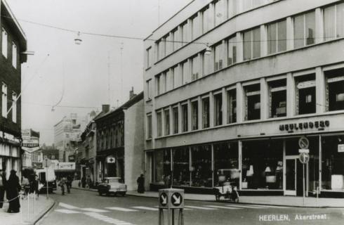 Bron: Rijckheyt.nl | Akerstraat. Rechts winkelpand Meulenberg. Links Foto Bonke. Op de achtergrond het Glaspaleis.