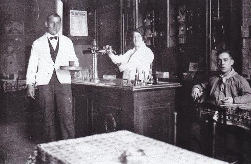 Bron: privécollectie | Achter het buffet de moeder van Liek van den Hoop, C. van den Hoop - Hanssen                       Man met wit jasje: De ober Wiel Erens, de man aan de tafel is een gast