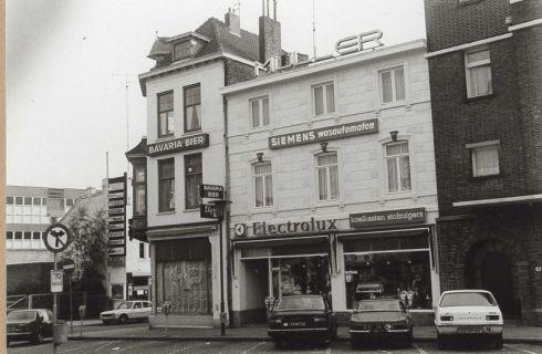 Bron: Rijckheyt.nl | Wilhelminaplein (14-9-1977). Links de Klompstraat met een gedeelte van het magazijn van Vroom & Dreesmann en de Rijwielbeurs. Op het Wilhelminaplein van links naar rechts: Elysee-bar; de winkel in witgoed F.J.Müller; en het Grand Hotel.