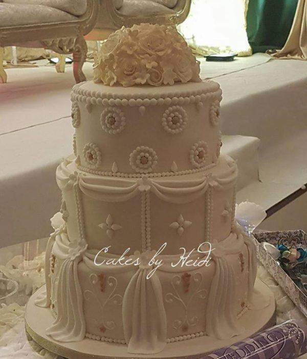 Three tiered elegant cream wedding cake