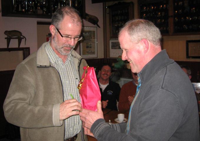 Peter (links) ontvangt uit handen van onze voorzitter Janus van Hooff een cadeaubon en een fles wijn.