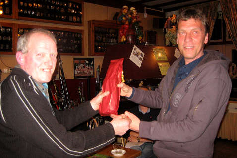 Ton (rechts) ontvangt uit handen van voorzitter Janus van Hooff een cadeaubon en een fles wijn.