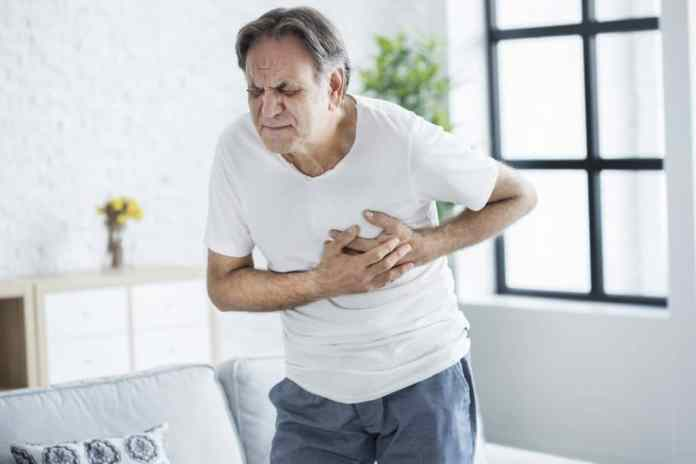 Old man holds his chest because of a heart attack