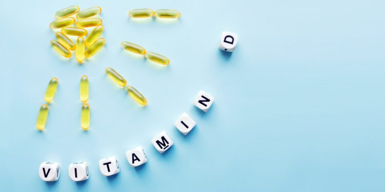 Yellow capsules shape a sun and sun rays;  including the lettering vitamin D.