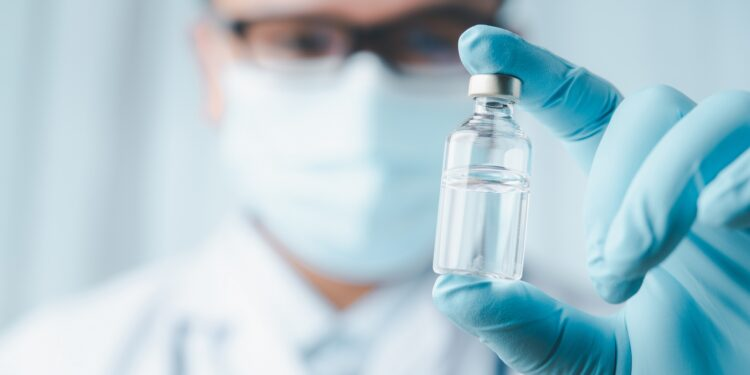 Medic holds vaccine ampoule between two fingers